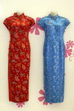 Chinese cheongsam gowns. On floral background Royalty Free Stock Images
