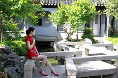 Chinese cheongsam model in Chinese classical garden. Chinese cheongsam model Sitting in stone chair,in the way, in Suzhou classical garden,Yan garden in stock images