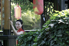 Chinese cheongsam model in Chinese classical garden. Chinese cheongsam model Sitting in wood bench under Red lantern,in a gazebo, in Suzhou classical garden, Royalty Free Stock Photos