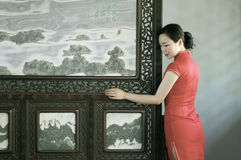Chinese cheongsam model in Chinese classical garden. Chinese cheongsam model standing beside the simple and elegant screen,in the doorway, in Suzhou royalty free stock photo