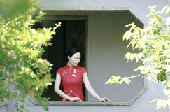 Chinese cheongsam model in Chinese classical garden. Chinese cheongsam model standing beside the windows on the wall,in the house, in Suzhou classical garden, Royalty Free Stock Photos