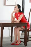 Chinese cheongsam model Sit on a stool. Chinese cheongsam model standing beside the simple and elegant screen,in the doorway,play in a famous garden.Qiyuan Royalty Free Stock Photo