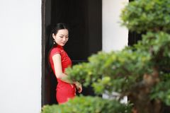 Chinese cheongsam model stand next to bonsai Royalty Free Stock Photos
