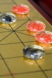Chinese chess. Golden chessboard and transparent chesses Royalty Free Stock Photo
