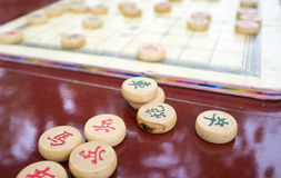 Chinese chess. Board game with round wooden pieces on red table Royalty Free Stock Photography