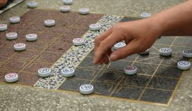 Chinese Chess Game. In the Park with Closeup of Hand Moving the Pieces Stock Photography