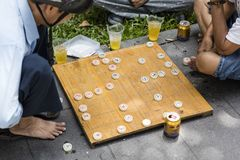Chinese chess. Unidentified man playing traditional Chinese chess on Ho Chi Minh sidewalk in Vietnam. It is one of the most popular board games in China Royalty Free Stock Photo