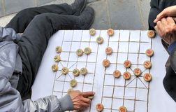 Chinese Chess (xiangqi ). A man makes a move on a on a local Beijing Chinese chess game board. Xiangqi, also known as Chinese chess, is an ancient board game Stock Photos