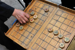 Chinese Chess (xiangqi). A man makes a move on a on a local Beijing Chinese chess game board. xiangqi, also known as Chinese chess, is an ancient board game Royalty Free Stock Photos