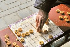Chinese Chess (xiangqi ). A man makes a move on a on a local Beijing Chinese chess game board. Xiangqi, also known as Chinese chess, is an ancient board game Royalty Free Stock Image
