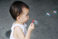 Chinese child  blowing bubbles Royalty Free Stock Photos