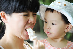 Chinese child eating ice cream with mother Royalty Free Stock Photo