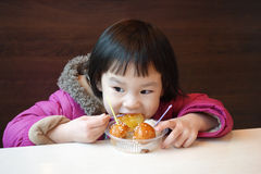 Chinese child eating snacks Stock Photos