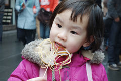 Chinese child eating sugar Royalty Free Stock Image
