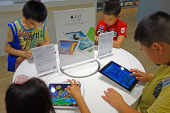 Chinese child playing ipad. In the apple retail store, Chengdu, China Royalty Free Stock Image
