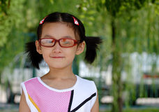 Chinese children lovely. Girl in the gardens, with a glasses Royalty Free Stock Images