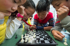 Chinese children playing chess in a school Stock Photography