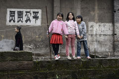 Chinese children. Smiling young Chinese children gather on a wall in the small village of Sichuan Province, China royalty free stock image
