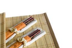 Chinese chopsticks. On bamboo place mat on white stock image