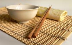 Chinese chopsticks on bamboo. An empty plate and chopsticks on bamboo rug Stock Images