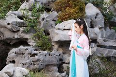 Chinese classic beauty in traditional ancient drama costume stand by rockery Royalty Free Stock Image