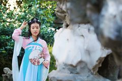 Chinese classic beauty in traditional ancient drama costume stand by rockery. Chinese beauty in traditional ancient costume, hold a fan on hand, elegant people stock photos