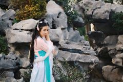 Chinese classic beauty in traditional ancient drama costume stand by rockery. Chinese beauty in traditional ancient costume, hold a fan on hand, elegant people stock images