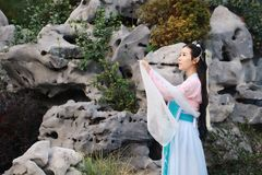 Chinese classic beauty in traditional ancient drama costume stand by rockery Stock Photography