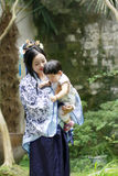 Chinese classic woman in Hanfu dress enjoy free time with baby and close friends Royalty Free Stock Image