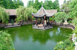 Landscaping gazebo Chinese garden. Asian Chinese classical garden and building in ancient oriental style.  Chinese classic pavilion gazebo on the pond in Stock Photo