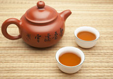 Chinese clay tea pot with two cups of tea on a straw mat. Transl royalty free stock photography