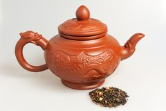 Chinese clay teapot with handful of green tea Royalty Free Stock Photography