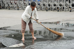 Chinese cleaner is sweeping street Stock Photos