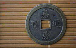 Chinese coin. Whit hieroglyphs on a bamboo Royalty Free Stock Image