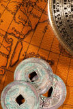 Chinese coins and compass over antique map Royalty Free Stock Photo