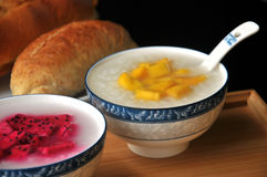 Chinese congee in bowl. Congee with Mango and dragon fruit in bowl Stock Images