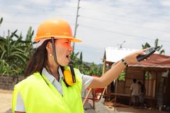 Chinese construction engineer directing. Pointing young Chinese female engineer with hardhat, directing and supervising a residential tropical construction site Royalty Free Stock Image
