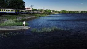 Chinese contemporary dancer in white shirt and black hat. Chinese contemporary dancer in white shirt and black hat is performing on the pier next to the river stock video footage