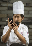 Chinese cook checking his two phones Stock Image