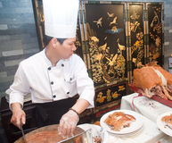 Chinese cooks in cutting roast pork Royalty Free Stock Photos