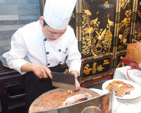 Chinese cooks in cutting roast pork Stock Photos
