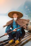 Chinese Cormorant Fisherman. Cormorant fisherman and his bird on the Li River in Yangshuo, Guangxi, China Stock Images