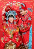 Chinese couple dressed in wedding ress. Closeup photo of Chinese young couple dressed in traditional wedding suite in typical Chinese wedding ceremony stock photo