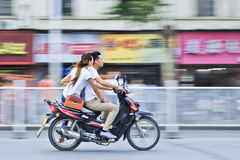 Chinese couple on gas motorcycle. XIANG YANG-CHINA-JULY 1, 2012. Couple on gas motorcycle on July 1, 2012 in Xiang Yang. Demand for gas motorcycles in China Stock Images