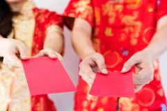 Chinese couple giving Ang Pao money. Hands of Chinese couple with red traditional cheongsam dress giving red evelope with Ang Pao money to children relatives Stock Image