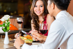 Chinese couple having romantic dinner in fancy restaurant. Asian Chinese couple - Man and women - or lovers flirting and having a date or romantic dinner in a Royalty Free Stock Photo