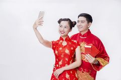 Chinese couple holding good luck item for new year. Chinese couple wear red to celebrate chinese new year smiling with the ang bao and hangings Royalty Free Stock Photo