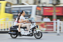 Chinese couple on a motorcycle. XIANG YANG-CHINA-JULY 1, 2012. Couple on gas motorcycle on July 1, 2012 in Xiang Yang. Demand for gas motorcycles in China Royalty Free Stock Photography