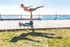 Chinese couple practicing acrobatic yoga at park in Toronto. Asian men and woman, the boy is holding the girl in the hair with his legs, both with open arms Royalty Free Stock Photos