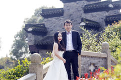 A Chinese couple`s wedding photo. Shot in park of water in Shanghai, young couple, bride with white wedding dress, groom wears suit. stand on an ancient stone Royalty Free Stock Photos